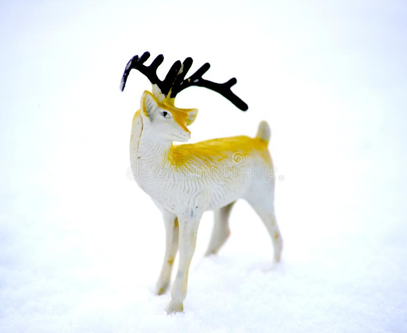 Deer figurine toy on a snow, winter theme. Image royalty free stock photos