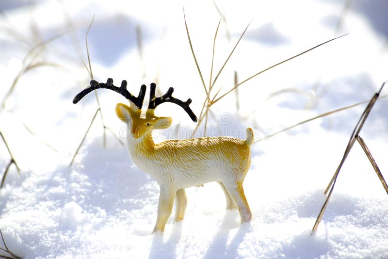 Deer figurine toy on a snow, winter theme. Image royalty free stock image