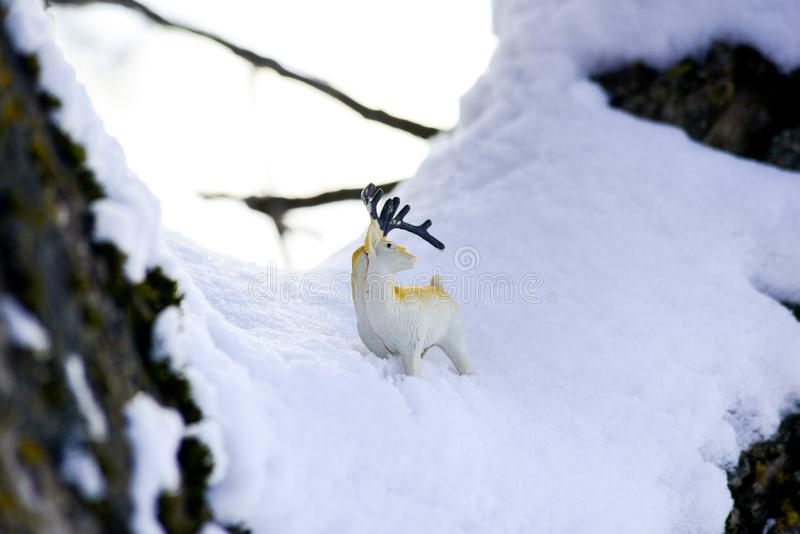 Deer figurine toy on a snow, winter theme. Image royalty free stock photo