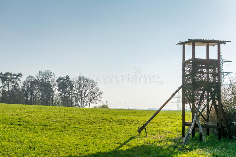 A deer stand in front of a meadow in the Natural Reserve schoenbuch in Germany royalty free stock images