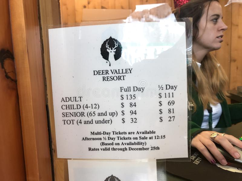 Deer Valley employee and lift ticket price list. Park City, UT, December 25, 2017: Deer Valley employee is issuing a lift ticket in the background behind a price royalty free stock photo