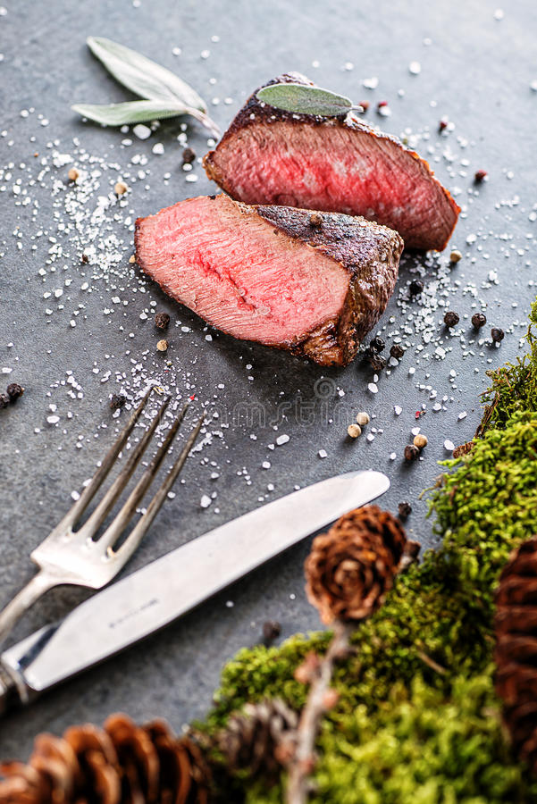 Deer or venison steak with ingredients like sea salt, herbs and pepper and cutlery, food background for restaurant or hunting lovi stock photo