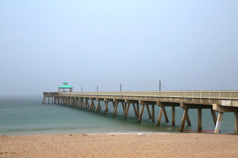 Deerfield Beach Pier in Rain. A giant sheet of rain in a gray overcast sky is imminent as it rapidly approaches the Deerfield Beach, Florida Pier in a cool royalty free stock photography