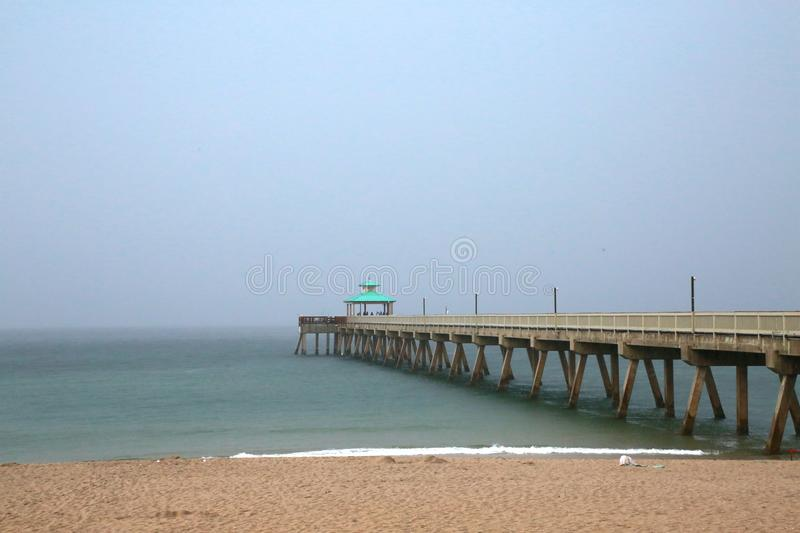Deerfield Beach Pier in Rain. A giant sheet of rain in a gray overcast sky is imminent as it rapidly approaches the Deerfield Beach, Florida Pier in a cool royalty free stock photos