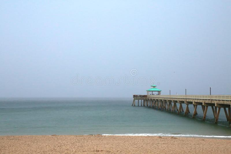 Deerfield Beach Pier in Rain. A giant sheet of rain in a gray overcast sky is imminent as it rapidly approaches the Deerfield Beach, Florida Pier in a cool stock image