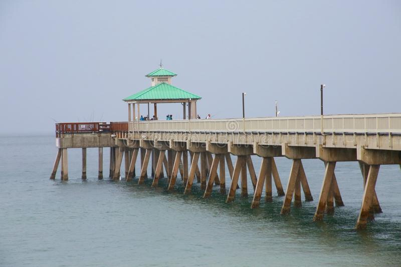 Deerfield Beach Pier in Rain. A giant sheet of rain in a gray overcast sky is imminent as it rapidly approaches the Deerfield Beach, Florida Pier in a cool stock photography