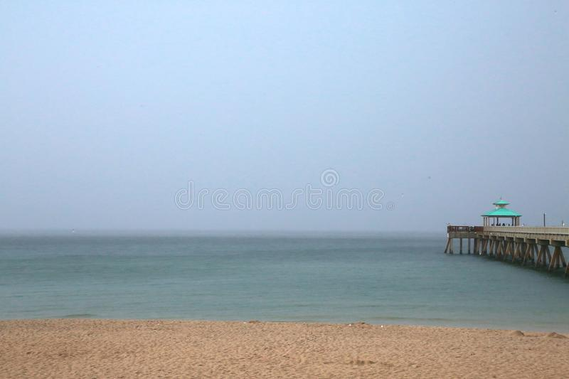 Deerfield Beach Pier in Rain. A giant sheet of rain in a gray overcast sky is imminent as it rapidly approaches the Deerfield Beach, Florida Pier in a cool royalty free stock image