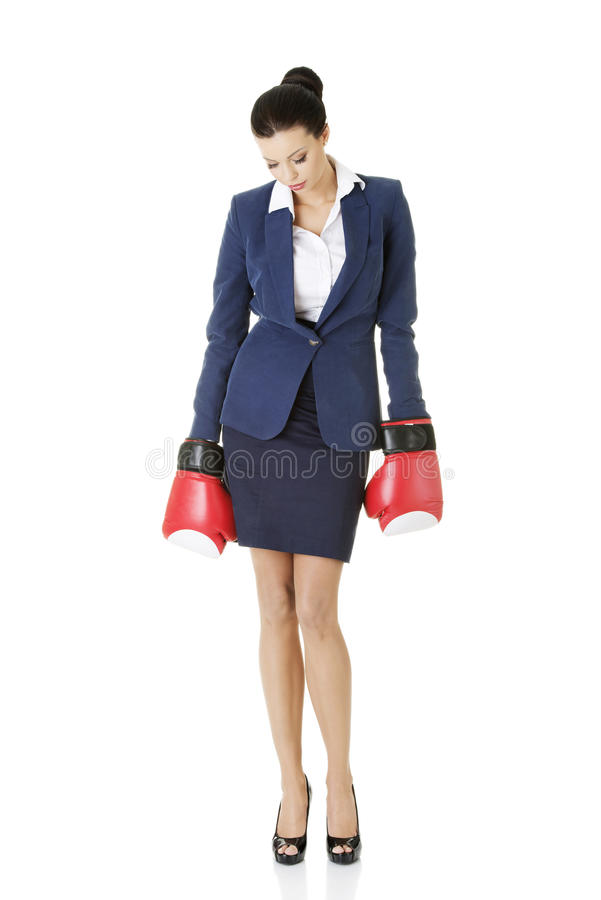 Defeated businesswoman in boxing gloves stock images