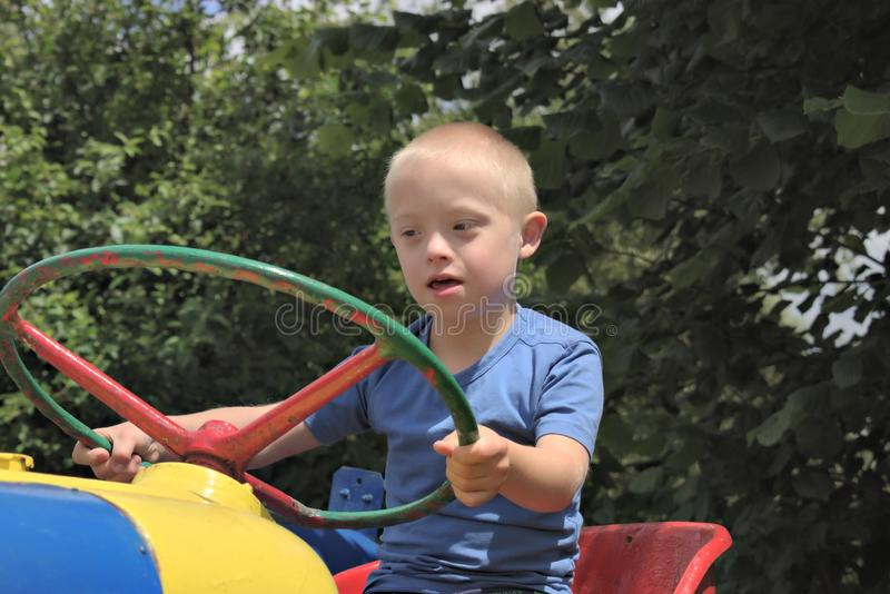 Boy with a down syndrome who is playing in a park. Defect,childcare,medicine and people concept- young boy with a down syndrome who is playing in a park royalty free stock photos