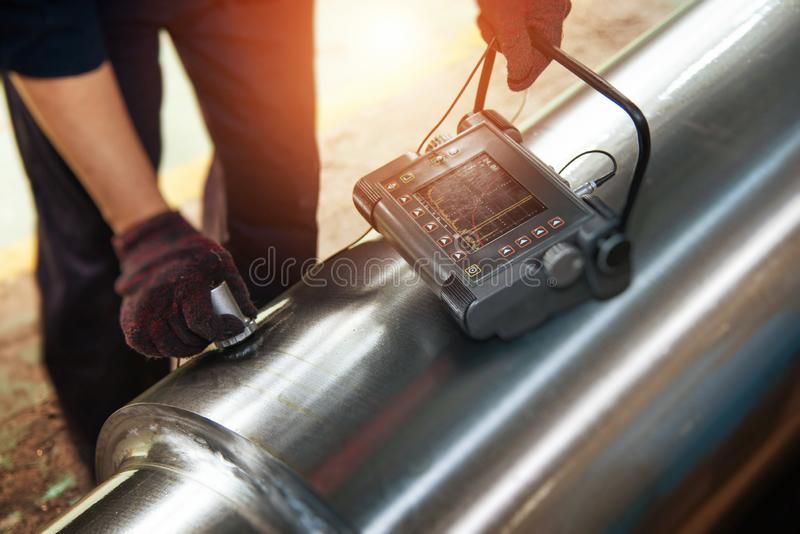 Defect Detection of Metal Materials. Technicians use flaw detectors to detect cracks or defects in metal pipes stock image