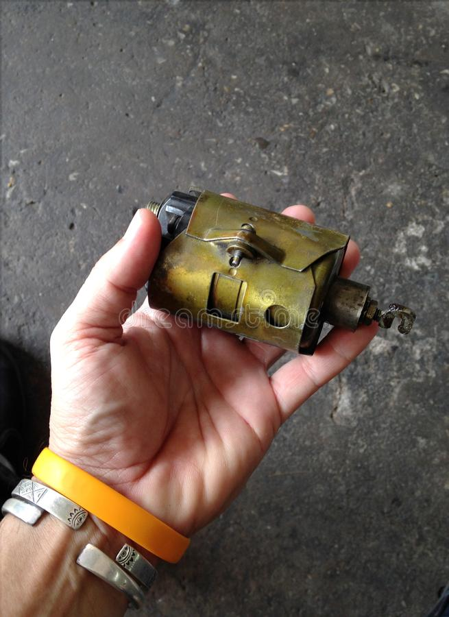 Defect worn out solenoid part disassembled from old gasoline starter motor engine. Service technician hand holding defect worn out solenoid part disassembled stock image