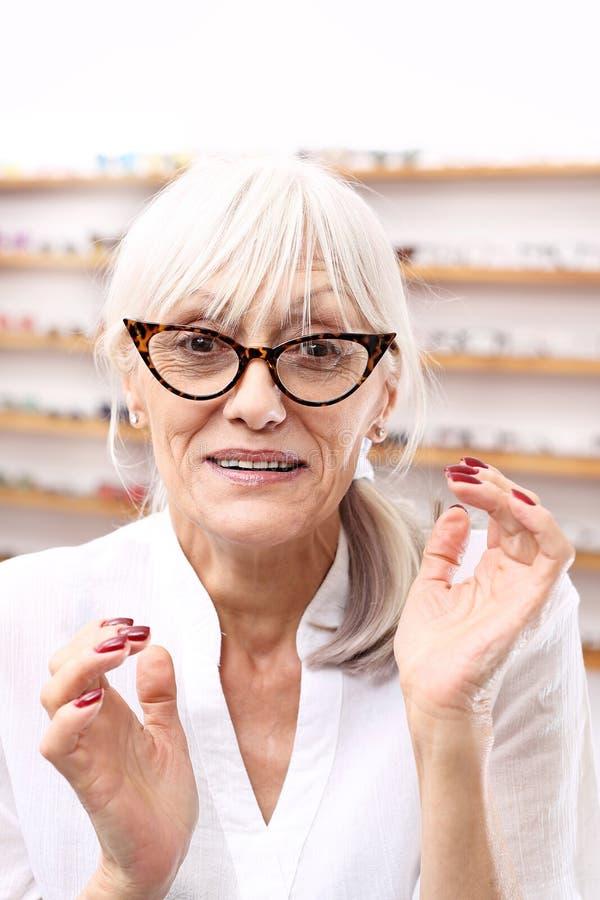 Defekt av vision En hög kvinna i en optisk salong väljer monokelramar royaltyfri fotografi
