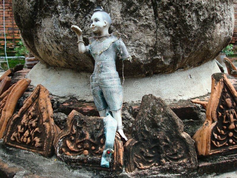 Defekte blaue thailändische Puppe, die unter den historischen Ruinen in Ayutthaya, Thailand anbietet lizenzfreies stockfoto