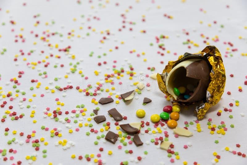 Defekte goldene SchokoladenOstereier mit bunten Schokoladen nach innen auf wei?em Hintergrund mit bunten unscharfen Konfettis stockfoto