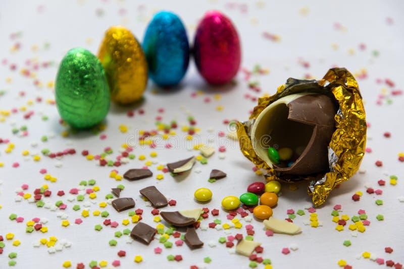 Defekte goldene SchokoladenOstereier mit bunten Schokoladen nach innen auf wei?em Hintergrund mit bunten unscharfen Konfettis und lizenzfreie stockfotos