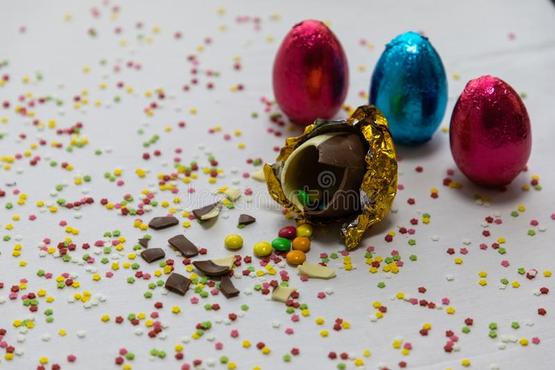 Defekte goldene SchokoladenOstereier mit bunten Schokoladen nach innen auf wei?em Hintergrund mit bunten unscharfen Konfettis und lizenzfreies stockbild