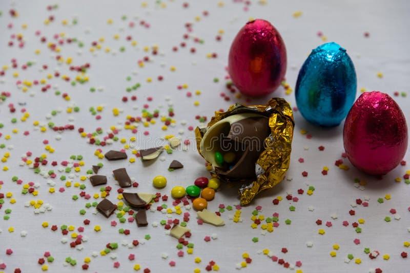 Defekte goldene SchokoladenOstereier mit bunten Schokoladen nach innen auf wei?em Hintergrund mit bunten unscharfen Konfettis und lizenzfreie stockfotografie