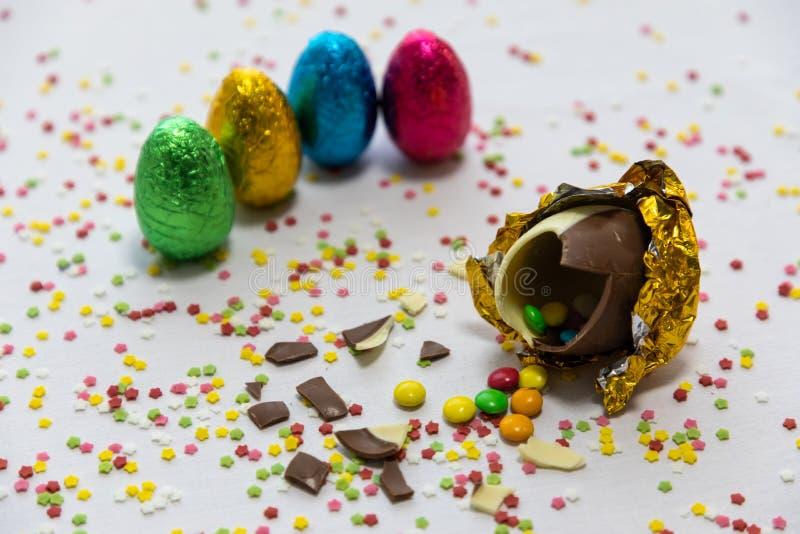 Defekte goldene SchokoladenOstereier mit bunten Schokoladen nach innen auf wei?em Hintergrund mit bunten unscharfen Konfettis und lizenzfreies stockfoto
