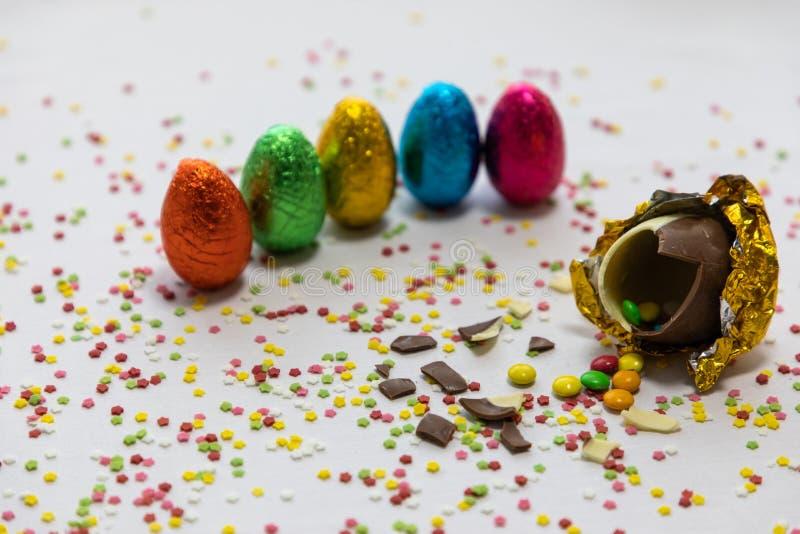 Defekte goldene SchokoladenOstereier mit bunten Schokoladen nach innen auf wei?em Hintergrund mit bunten unscharfen Konfettis und lizenzfreie stockbilder
