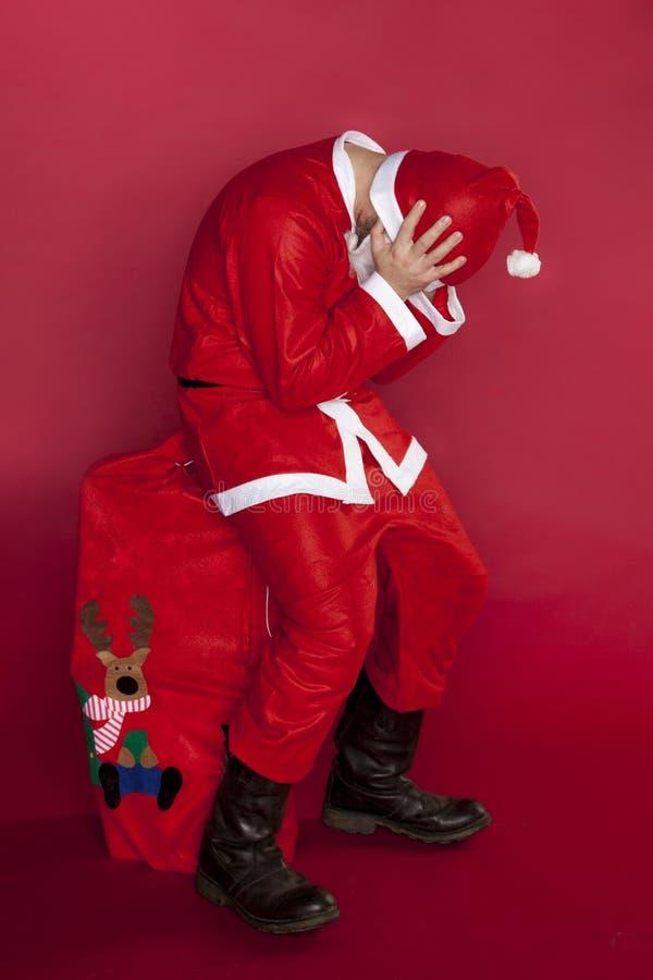 Defekte Santa Claus, die auf einer Tasche angefüllt mit Geschenken sitzt lizenzfreies stockbild