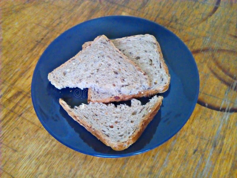 Defekte Stücke Brot auf einer Platte auf einer alten, schäbigen Küchenholzoberfläche stockbild
