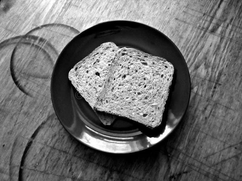 Defekte Stücke Brot auf einer Platte auf einer alten, schäbigen und schäbigen Küchenholzoberfläche stockbilder