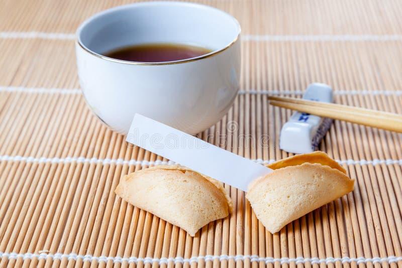 Defekter Glückskeks mit Beleg und Essstäbchen und Tee stockfotografie
