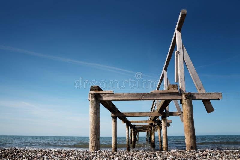 Defekter hölzerner Pier oder Anlegestelle führt in das Meer gegen eine blaue SK lizenzfreie stockfotografie