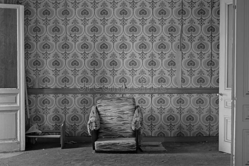 Defekter Lehnsessel auf schmutzigem Teppich und heftiger Tapete lizenzfreie stockbilder