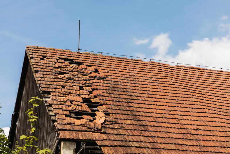Defekter Ziegelstein bauscht sich auf dem Dach eines Häuschens stockfotos