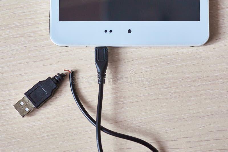 Defektes usb-Kabel auf einem Holztisch stockbild