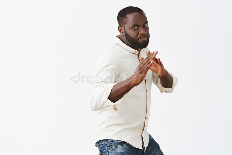Defend yourself. Portrait of serious-looking strong and funny dark-skinned male model in white casual short standing in. Martial arts pose, ready to fight stock image