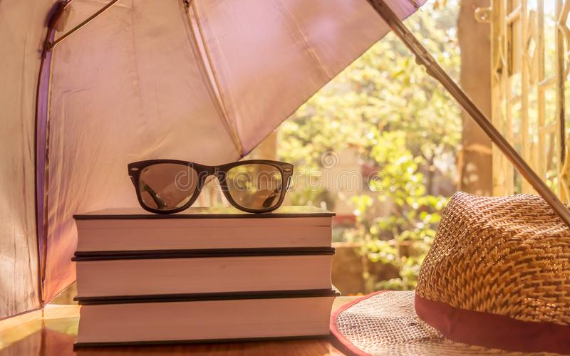 Defending light beams with umbrella. Umbrella protecting beautiful woman things. Books sunglasses and a straw hat. Summer holiday. Concept with copy space room stock photography