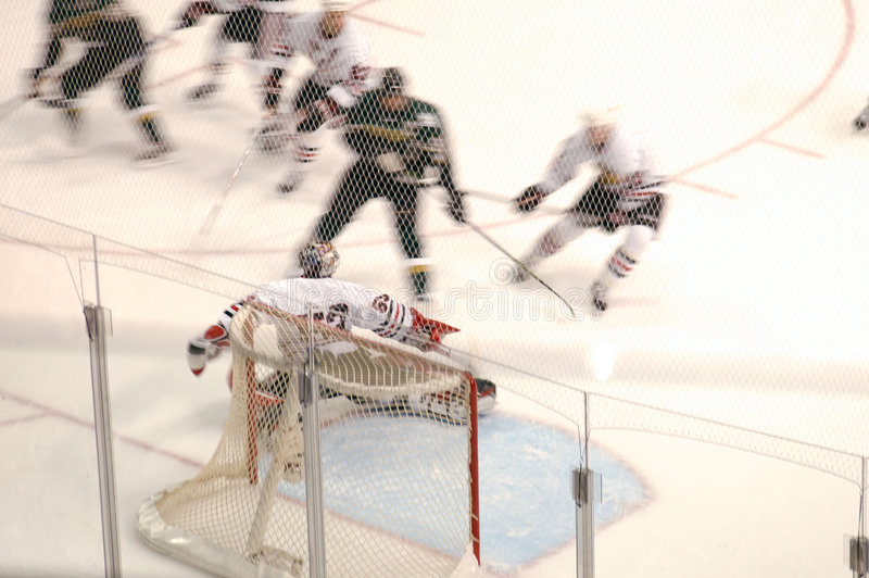 Defense. Goalie protects the goal as many hockey players converge on him stock photography
