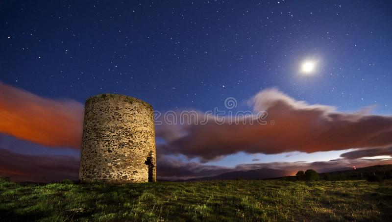 Old fortified cylinder or round tower in ruins under moonlight night starry and cloudy sky. Defensive round old medieval tower under starry night sky. The stock photo