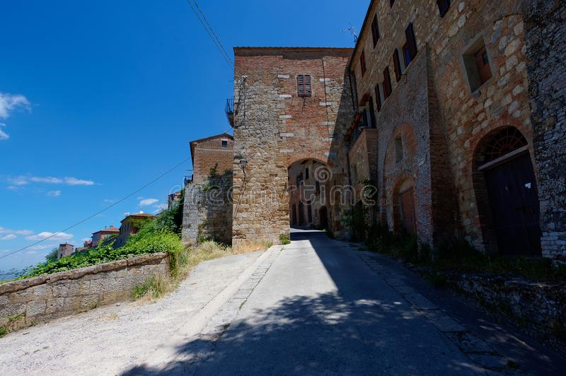 Defensive wall, Montepulciano, Tuscany, Italy. Surrounding defensive wall and gate, and landscape in the sun under the blue sky and strong shadow of stock images