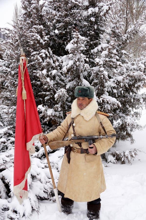 Defensor de Stalingrad em um formulário do inverno com uma bandeira vermelha fotografia de stock royalty free