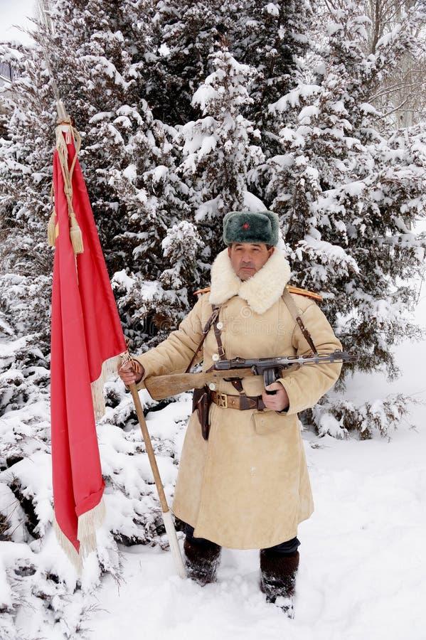 Defensor de Stalingrad em um formulário do inverno com uma bandeira vermelha foto de stock