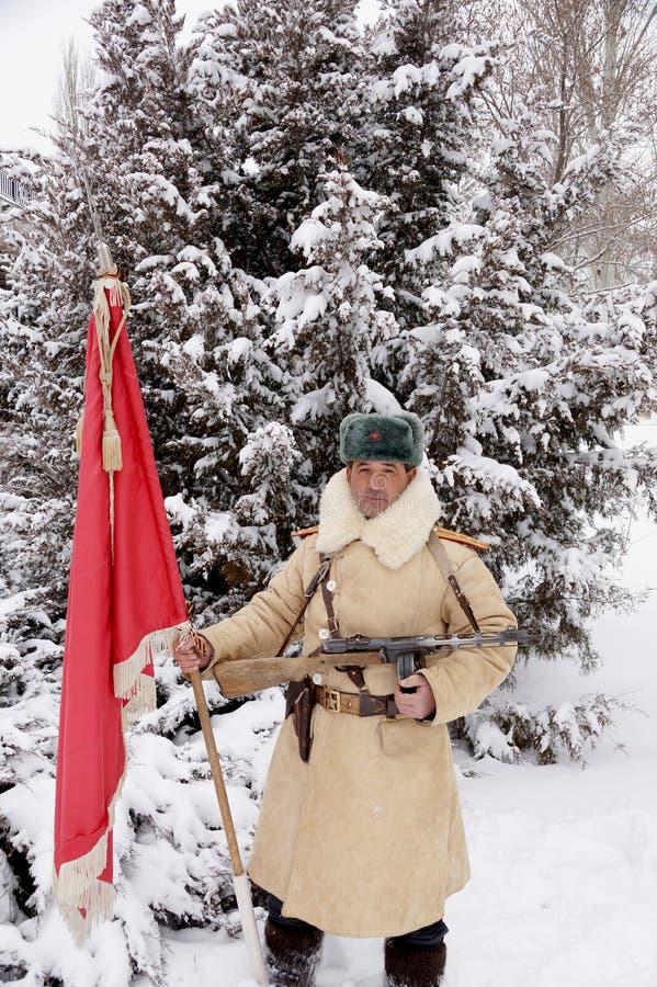Defensor de Stalingrad em um formulário do inverno com uma bandeira vermelha imagem de stock
