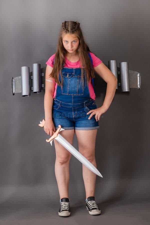 Defensor militante de la muchacha con una espada y un jetpack imagen de archivo libre de regalías