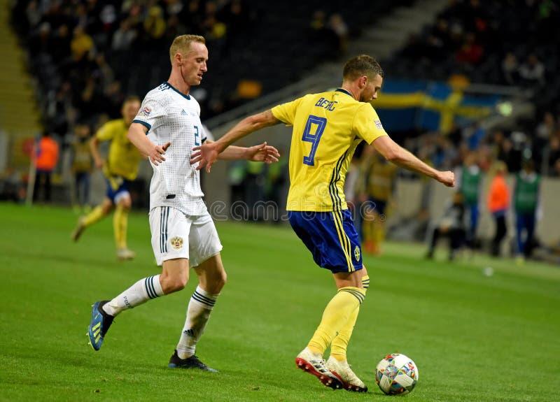 Defensor Vladislav Ignatyev da equipe nacional de Rússia e de equipe nacional da Suécia grevista Marcus Berg imagens de stock