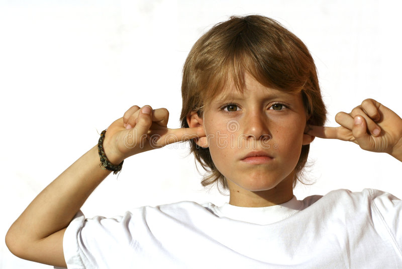 Defiant child fingers in ear. Defiant angry child fingers in earns stock photo