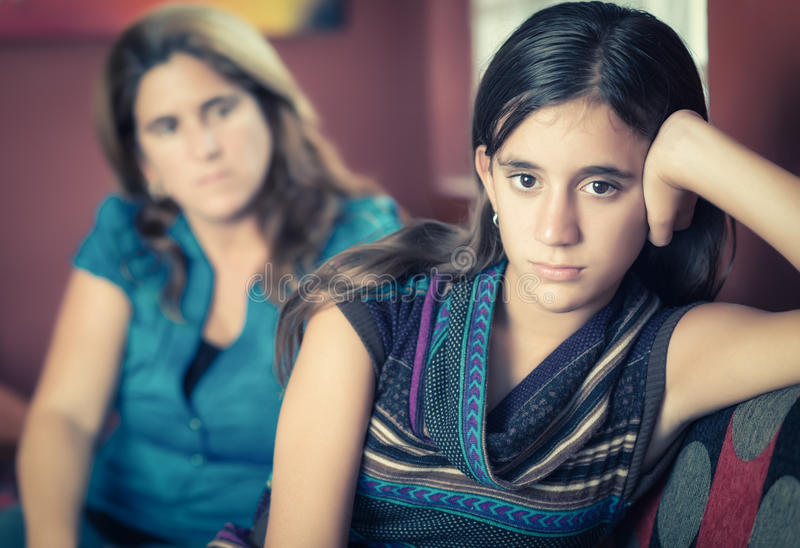 Defiant teenage girl and her worried mother. Teenager problems - Defiant teenage girl after a fight with her worried mother looking at her royalty free stock photo