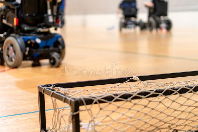 Deficientes motores em uma cadeira de rodas elétrica que joga esportes, hóquei do powerchair IWAS - Cadeira de rodas e amputado i imagem de stock