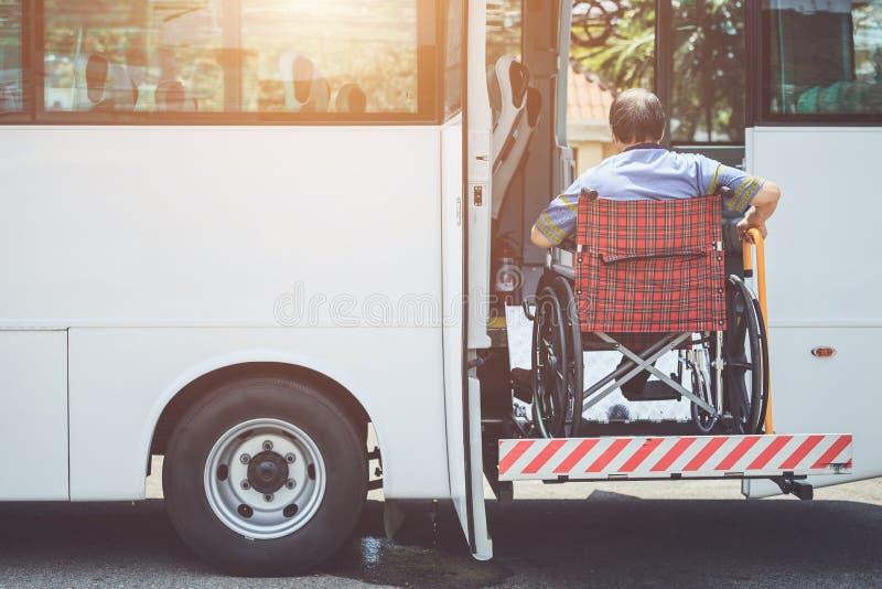 Deficientes motores que sentam-se na cadeira de rodas e que vão aos bu públicos imagem de stock royalty free