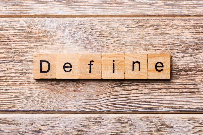 Defina la palabra escrita en el bloque de madera Defina el texto en la tabla de madera para su desing, concepto fotografía de archivo
