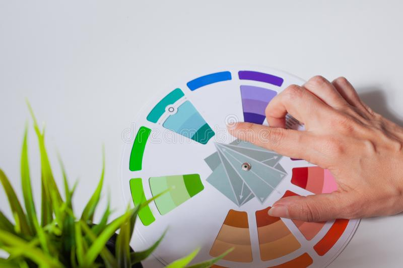 Define your color type. Female hands with neat, concise manicure rotate the color wheel. The color circle lies on a white background, next to a green plant royalty free stock images