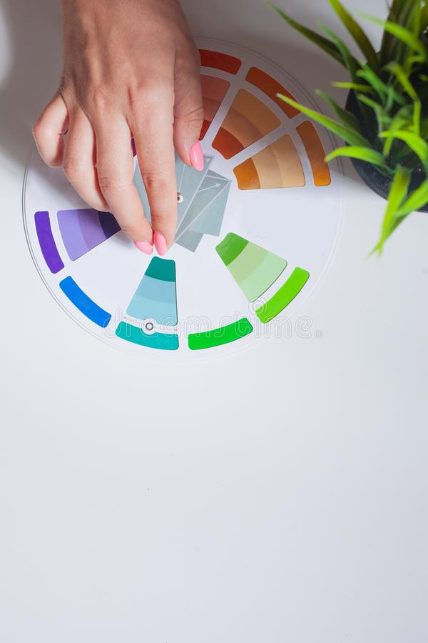Define your color type. Female hands with neat, concise manicure rotate the color wheel. The color circle lies on a white background, next to a green plant royalty free stock photo