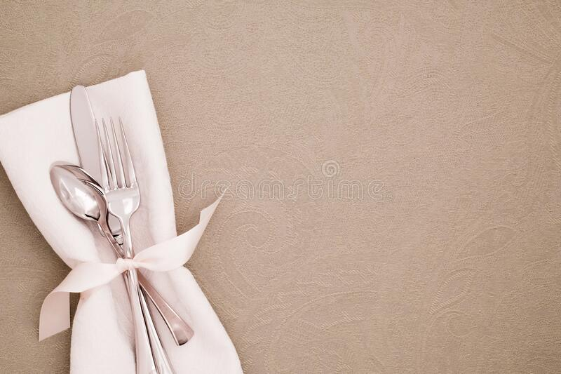 Definição de Local da Tabela com Silverware e guardanapo de pano Branco em Tablecloth Beige Brocade como fundo com espaço de cópi foto de stock royalty free