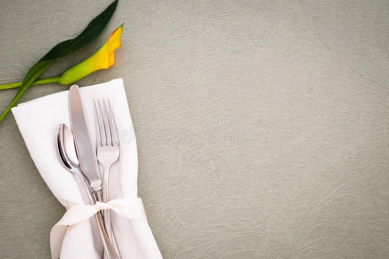 Definição de Local da Tabela com Silverware, Flor Amarelo e guardanapo de pano Branco na Tablecloth de Brocade Cinza como fundo c fotografia de stock
